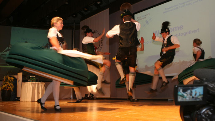 Group photo: several people in traditional Bavarian dress dance the Schuhplattler.