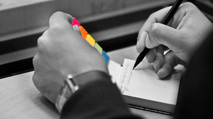 Detail image: A person's left hand is holding an opened notebook, while the right hand is taking a note with a pencil.