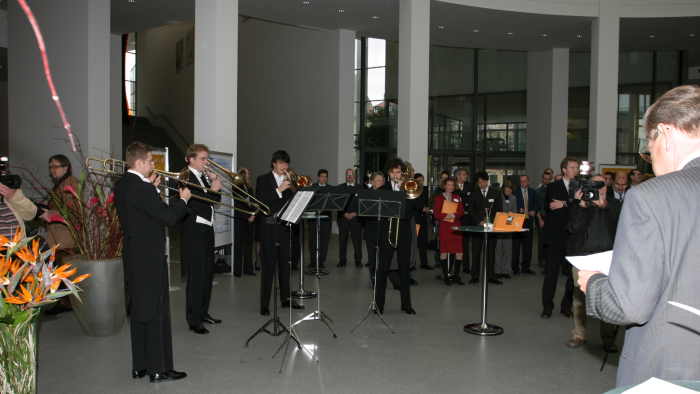 Group photo: a brass ensemble plays a piece of music in front of an audience.