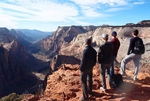 Three young people stand at the edge of a canyon and look into the distance.