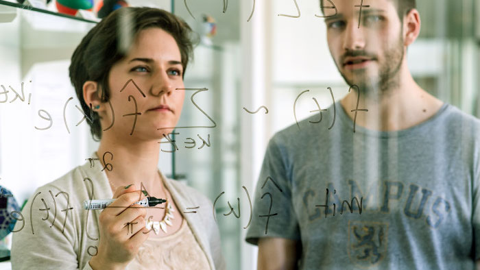 A woman and a man look at a scientific formula written on a glass board.