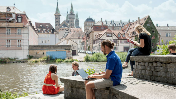 Young people sit on stone steps by a river and study.