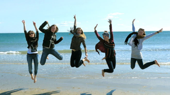 Photo of numerous students at a beach, leaping into the air.